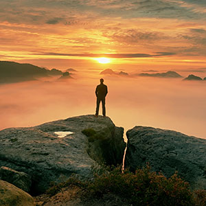 Man standing on rock looking at sunset